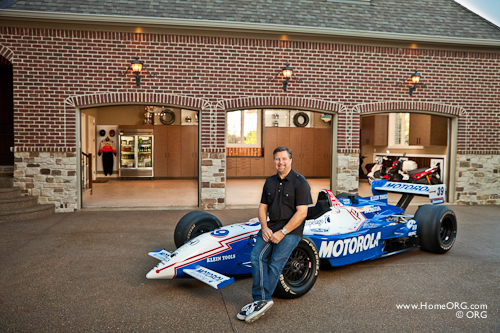 Michael Andretti and race car outside his home garage.
